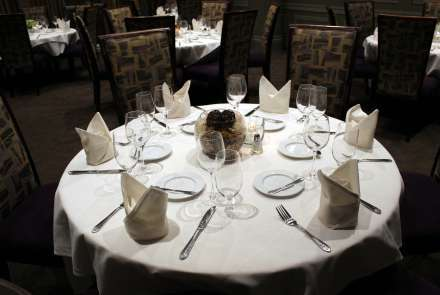 A round table set for 6, with white tablecloth, cloth napkins, silverware, stemware, and bread plates. Similar round tables are seen in the background.
