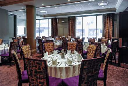 A room with large windows, round tables seating 8, and high backed chairs with velvery purple seats
