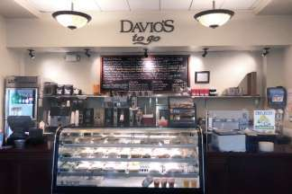 Davio's Boston To Go Shop features hot coffee, soup, and cookies behind the counter, a refrigerated case with salads and sandwiches, and a chalkboard overhead detailing the daily specials