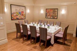 Colorful painting adorn the walls of this room with a table set for 12.