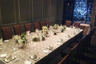 The Washington Room with a long table set for 16. Through the window, the trees outside are lit for the holidays.