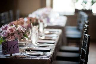 Rectangular tables set with centerpiece bouquets of pink roses, light coming through the window with the background in soft focus