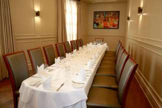 A long table with a white tablecloth, set for 18